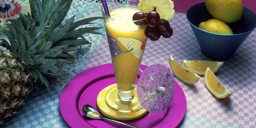 Couple fruits on cup of glass with lemon water